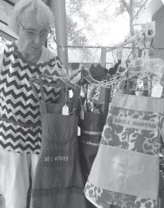 Louise Duncan shows off her handmade aprons at the Farmer's Market. Their stand included fresh sourdough bread, handmade aprons, bird houses and plants.