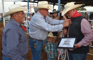 Darryl Ashley (center) fixes the neckerchief slide on his son, Derek (right), as he was named the Working Cowboy of the Year. TOM FIRME | PLEASANTON EXPRESS