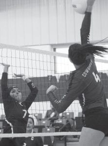 Charlotte's Julissa Cantu (left) goes up for a block as McMullen's Caroline McClaugherty (right) spikes the ball during Tuesday night's area matchup. REBECCA PESQUEDA | PLEASANTON EXPRESS