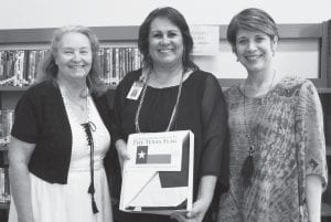 Pictured with Poteet Librarian Lisa Burbridge (center) are Pat Tuoy (left) and Karen Gerstenherber (right) of the Tocker Foundation. Burbridge is holding a Texas Flag donated to the library by the Tocker Foundation. The Poteet Public Library received a $50,902 grant from them for the shelving and furniture of the new building. REBECCA PESQUEDA | PLEASANTON EXPRESS