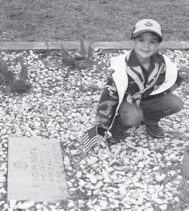 Tristan Tijerina, Wolf Cub Scout placing a flag on a Veteran's grave on Nov. 10 at the Pleasanton City Cemetery.