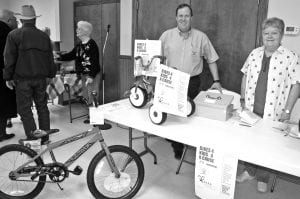 Jeff Chicoine and Dorothy Manning are pictured selling raffle tickets at the Santa event in Jourdanton on Dec. 3. The prize drawing for a chance to win a bike is a project of the Jourdanton Rotary Club. LISA LUNA | PLEASANTON EXPRESS