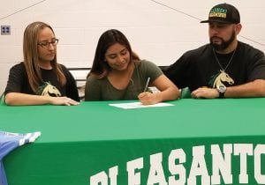 Messiah San Miguel (center) signs her letter of intent to Laredo College with father Mando San Miguel (right) and stepmother Jessica Ottinger (left) looking on. TOM FIRME | PLEASANTON EXPRESS