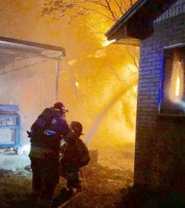 Firefighters work to contain the flames at the structure fire on Brown and Olive St. last Tuesday night. JACK GARCIA