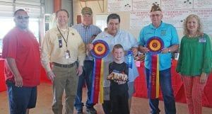 Bridger Ross won Grand Champion in the Junior Division with his Strawberry Monkey Bread. It sold for $950 to buyers, from left, Jay Dominguez- Silver Eagle Distributors-Bud Light, Ron Mixon-Poteet Rotary Club, Bill Arlitt-Best 1 Hummingbird Feeders, Richard Castillon-Cricket Wireless, John Shipley-Poteet VFW and Aubrey Smith-H-E-B. Up front is Bridger with his entry. NOEL WILKERSON HOLMES | PLEASANTON EXPRESS