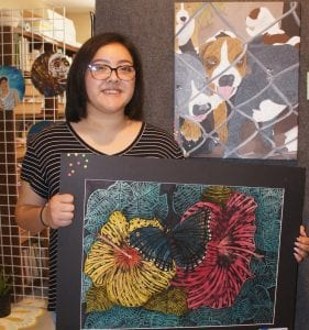 PHOTO AT LEFT: Alaina Caballero displays her artwork at the art show. She earned a State medal at the Visual Arts Scholastic Event in San Marcos.