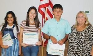 Conservation Essay Award recipients are, from left, Kloe Mogg, 3rd place; Abi Dumas, 2nd place; and Samuel Green, 1st place., Presenting the awards is Tina Clyburn. LEON ZABAVA | PLEASANTON EXPRESS