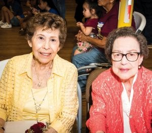 Mary Zuniga is the only surviving child out of the 12 Zuniga children. She is wearing yellow and is pictured with her sister-in-law, Genoveva Zungia (who was married to Amado Zuniga).