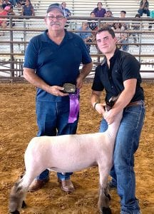 Logan Johnson of Victoria with his Medium Wool Sheep who had the Grand Honors at the Show. Logan is pictured with Atascosa County Fair President Jay Korus. COURTESY PHOTO