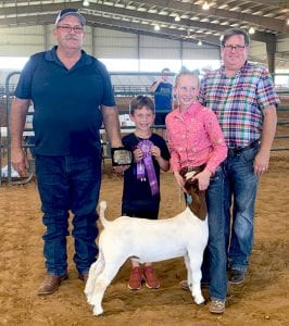 Addison Rouse of Kennedy took home Grand Champion Honors at the Goat Show. Addison is pictured with Jay Korus Atascosa County Fair President, brother, Kipton Rouse and judge Chad Coburn from Sterling City. COURTESY PHOTO