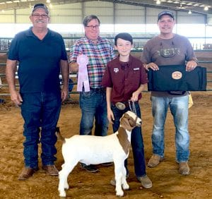 Memphis Landa of Poteet had the Reserve Grand Champion Goat. Pictured with Memphis is Jay Korus Atascosa County Fair President, Chad Coburn judge from Sterling City and father Usvaldo Landa of Poteet. COURTESY PHOTO