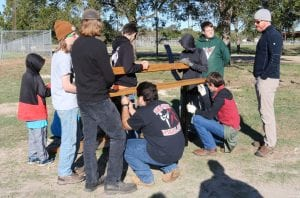 Scouts with Boy Scouts Troop 194 help assemble memorial benches at the Pleasanton River Park.
