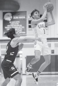 Kameron Parks (1) drives in for a layup against Poteet's Giovani Magirl on Friday night. J GARCIA | COURTESY PHOTO