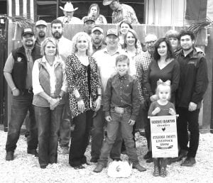 RESERVE GRAND CHAMPION BROILERS From La Parita 4-H, Holden Pawelek's Reserve Grand Champion Broilers brought in $5,000 from buyers, from left: Richard DeLeon (Glazer-Lonestar), John Krauskopf (Bar 80 Cattle), Benita Muckleroy (First Commercial Bank), Ralph Goode (Glazers Beer & Beverage), Aubrey Smith (H-E-B), Tim Swan (Mac Haik Southway Ford), Chris Varnon (Bar 80), John Olle (Statewide Claim Services), Blair Varnon (Bar 80 Cattle), Sherry Gaydos (Gaydos Construction), Bob and Cheryl Price (Price Chevrolet), Cathy Pawelek and Zachary Price (Price Powersports). Up front are Holden Pawelek and his sister holding the banner, Emery. MEMORIES ON MAIN | COURTESY PHOTO