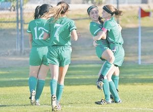 Madelyn Bird (right) hugs teammate Delanee Olivarri with teammates Kaitlyn Garcia (12) and Kenley Everett (7) joining the celebration after scoring a goal during the 2020 Battle of the Brush Country. J GARCIA | PLEASANTON EXPRESS