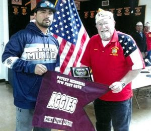 Jack Carrasco of the Poteet Aggies Little League presents Herman Hood of VFW Post 6970 in Poteet with a team picture plaque and Poteet Aggies Little League flag runner. The presentation was made to thank Post 6970 for their support.