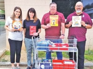 Poteet ISD provided 1,186 breakfasts and lunches to the community on Tuesday. They also handed out books to students to motivate them to keep reading. Pictured, from left are Poteet ISD staff members Amanda Gonzales, Sheryl Mills, Don Wildenstein and Superintendent Charles Camarillo.
