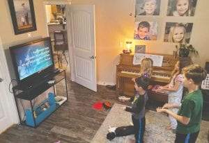 Abby and Pastor Pete Pawelek's children enjoy a live-streaming service of Cowboy Fellowship. Children are Ryder, Tatum, Hadley and Peter Pawelek.