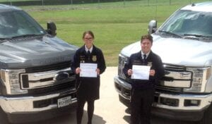 Reagan Moon and Cotton Harris are pictured with their scholarship certificates for $1,000 each through the National FFA Organization Built Ford Tough Ford Truck Scholarship Program. Kinsel Ford Three Rivers is the local sponsor for these scholarships. COURTESY PHOTO
