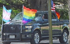 A vehicle bearing the Transgender flag, Pride flag and American flag leads the parade down a neighborhood street on Saturday. SAM FOWLER | PLEASANTON EXPRESS