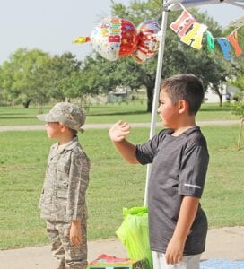 Liam Lambardia (right) waves at parade goers while his younger brother, Lukas, stands at attention in his Army uniform. REBECCA PESQUEDA | PLEASANTON EXPRESS