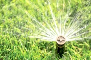 Sprinkler system watering a lawn.