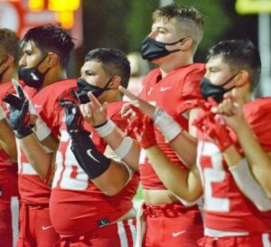 Emmanuel Lugo (far left), Isaac Paredes (56), Cole Andrus and Nick Cordova (12) lock fingers to sing Jourdanton's Alma Mater after their 56-35 loss to Calallen on Friday, Sept. 4. All of them are wearing masks as required by the UIL's COVID-19 Risk Mitigation guidelines. SAM FOWLER | PLEASANTON EXPRESS