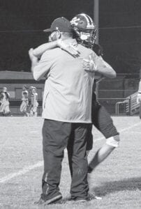Logan Wilson hugs a Lytle assistant coach after making a play in the Pirates' 21-20 overtime win over Randolph on Oct. 9. Wilson had the first touchdown of the game on Friday night. KYLIE MASK | LYTLE ISD