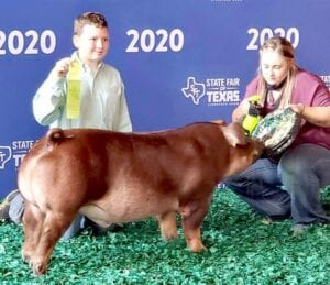 Jaxson Powell proudly displays his ribbon and Duroc after taking 7th place at the Texas State Fair. COURTESY PHOTO