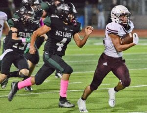 Ernest Davila races by Marion's Dominic Castellanos (4) for a big gain during Poteet's 29-22 win on Thursday night. Davila finished the game with 326 yards rushing and three touchdowns as Poteet grabbed sole possession of second place in District 14-3A DI. SAM FOWLER | PLEASANTON EXPRESS