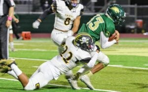 Daniel Aguirre (22) wrestles a Cole ball carrier to the ground during Lytle's 28-20 win over the Cougars on Thursday, Oct. 22. The narrow win kept Lytle's playoff hopes alive. KYLIE MASK | LYTLE ISD