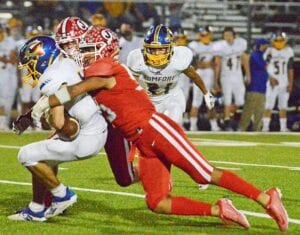 RIGHT: Senior defensive end Emmanuel Lugo swallows up Comfort quarterback Oscar Falcon for one of his three sacks on the night. Lugo had three sacks and six tackles for a loss in the Indians' 56-32 win over the Bobcats in the bi-district playoff on Saturday.