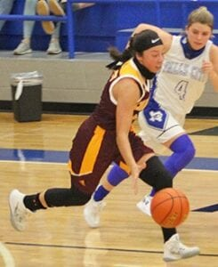 Mia Campos tries to get by a Falls City defender during the Trojanettes' loss on Jan. 5. Campos led the team in scoring with eight points. MERCEDES SANCHEZ | PLEASANTON EXPRESS
