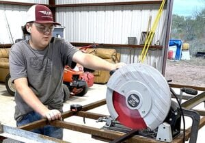"""Barker uses a dry cut chop saw to cut the 1"""" square tubing to correct lengths for the structure of the livestock scale. CHASE AND TABETHA BARKER"""