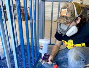 Barker uses a HVLP spray gun to apply the oil-based enamel paint. CHASE AND TABETHA BARKER