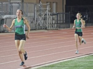 Caitlyn Nieschwitz and Kassidy Vickers push down the frontstretch of the 1600-meter run at the District 27-4A meet in Cuero on March 31. SAM FOWLER   PLEASANTON EXPRESS