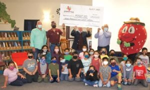 """Congratulations to the four classes at Poteet ISD that chose the name """"Strawberry Fields"""" as the name of the new subdivision being built. Pictured in the foreground are some of the students from the two winning elementary classes. In the back row with the $7,000 check are, from left: Jay Parker of Strawberry Fields, Poteet Mayor Willie Leal Jr., Tim Dillard representing Strawberry Fields, Poteet ISD Superintendent Charles Camarillo and Freckles, the Poteet Strawberry Festival mascot. LISA LUNA   PLEASANTON EXPRESS PHOTOS"""