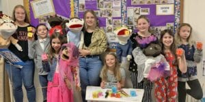Left to right: LTC students Mikayla Theis, Tristan Kunkel, Lily Cates, Laynie Bryan, Alina Miller, Mikenna Maxwell, Emilee Kunkel and Abby Schjang pose at Pleasanton Church of Christ in front of their bulletin board with puppets, props, art supplies and Bible Bowl blocks. MELISSA THEIS   PLEASANTON EXPRESS PHOTOS