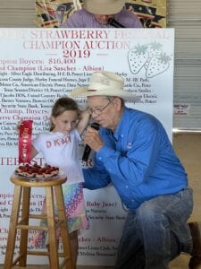 Briley Rakowitz with auctioneer Tommy Crouch displaying her Mini Cherry Cheesecakes. Briley is the daughter of Walt and Nichole Rakowitz. NOEL WILKERSON HOLMES PLEASANTON EXPRESS