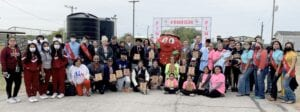 Group photo of some of the participants and volunteers in the first ever Poteet Strawberry Festival 5K and 1 Mile Berry Run/Walk, along with the Poteet Strawberry Festival Court and Freckles the mascot.