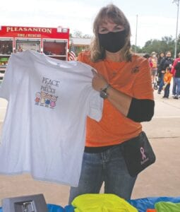 Wendy Saunders displays their T-shirts for sale. Shirts are still available to purchase for $10 each by calling Laura at 830-570-2782.