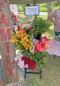 """The Olive Branch hosted a """"Make Your Own Bundle"""" floral booth at the Ropin' at the River Farmer's Market."""