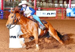 Emma Smith rounds a barrel on her horse Lola during a race in the 2021 season. Smith is excited about the opportunity to compete at the CNFR in her freshman season at Texas A&M University. PHOTO COURTESY OF JENNINGS PHOTOGRAPHY
