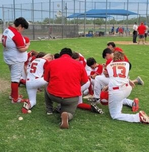 Members of the Jourdanton Little League Junior All-Stars pray before a game at the Texas West Section 3 tournament in San Angelo. The All- Stars finished second place at the three-day tournament with wins over Reagan County and Medina Valley. PHOTO COURTESY OF JOURDANTON LITTLE LEAGUE