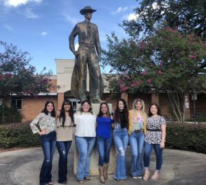 """Raylin Castillo, Cheyenne Garza, Erin Light, Autumn Guerra, Angel Turley, Ally Sherley, and Linda Sanchez are the 55th Cowboy Homecoming Queen candidates as they honor the """"Mr. Cowboy"""" sculpture in Pleasanton in front of the City Hall. GABRIELLA RUIZ 