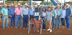 David Brandon Smith was named the 2021 Working Cowboy of the Year this past Saturday at the Pleasanton Young Farmers' Rodeo and Festival at the Atascosa County Show Barn. Pictured, from left, are Gus Wheeler of Atascosa County Livstock Exchange and saddle sponsor, Derek Ashley, Randy Rice, Darryl Ashley, Robert May (father-in-law), COY Brandon Smith, wife Marie Smith, daughter Emma Smith, Roy Alonzo, son Aydan Smith and parents Ann and David Smith. JOE DAVID CORDOVA   PLEASANTON EXPRESS