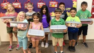 """K-3rd grade Journey Land kids with Smile Boxes they assembled for Mision Para Cristo's """"Smile for a Child"""" program. Back row, from left: Avery Miller, Jayce Bryan, Autumn Roberts, Noah De Leon and Emerson Royal. Front row: Jaylee Cate Maxwell, Kinsley Roberts, Everette Royal and Elijah De Leon. MELISSA THEIS 