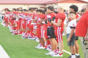 Above: The Jourdanton Indians hold miniature American flags during the national anthem before their game against Pleasanton last Friday night. JOE DAVID CORDOVA   PLEASANTON EXPRESS
