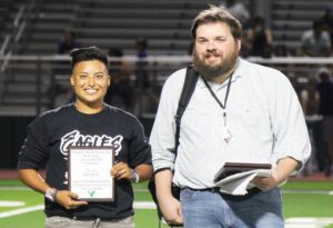 Above Left: Erica Lopez shows off her hall of honor plaque during halftime of the Eagles game against Boerne last Friday night. Above Right: Jason Guerra receives his hall of honor plaque from Pleasanton Express Sports Editor Stephen Whitaker. Ernest Monroe, the third member inducted, was not able to make the induction ceremony. STEFON TORRES & GAGE PAWELEK| PLEASANTON ISD
